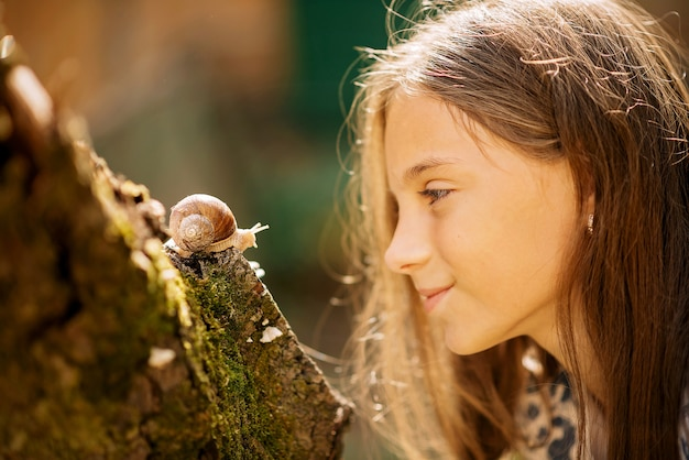 Joyful meeting of a little girl and a snail.