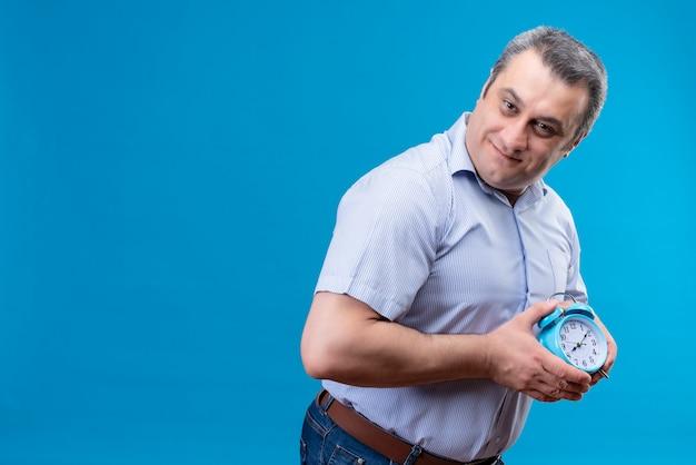 青色の背景に手で青い目覚まし時計を保持している青いストライプのシャツでうれしそうな中年男