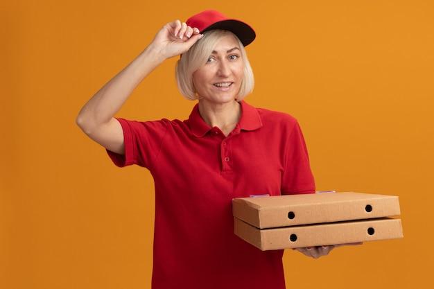 Радостная блондинка средних лет доставщица в красной форме и кепке держит упаковки с пиццей, глядя на переднюю кепку, изолированную на оранжевой стене