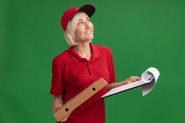 Gioiosa donna bionda di mezza età che consegna in uniforme rossa e berretto che tiene appunti e pacchetto pizza che guarda in alto