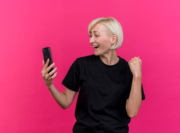 真っ赤な背景で隔離のイエスジェスチャーをしている携帯電話を保持し、見てうれしそうな中年金髪スラブ女性