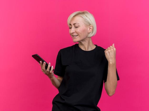 真っ赤な壁に隔離されたイエスのジェスチャーをしている携帯電話を持って見ているうれしそうな中年の金髪スラブ女性