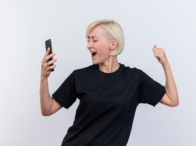 흰색 배경에 고립 된 닫힌 된 눈으로 예 제스처를 하 고 휴대 전화를 들고 즐거운 중 년 금발 슬라브 여자