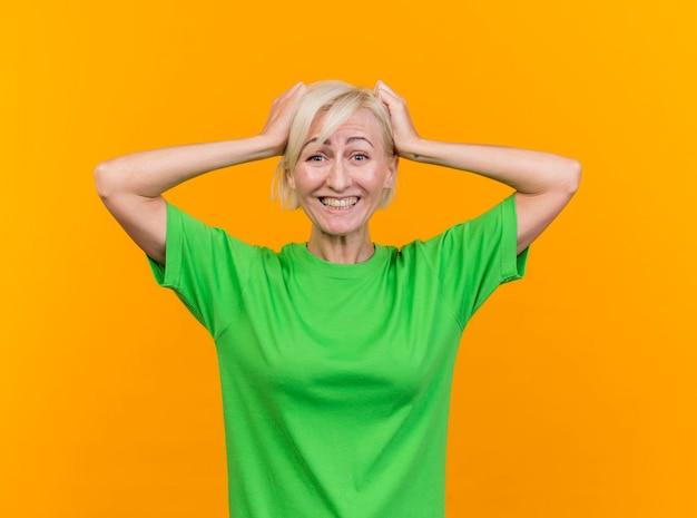 노란색 벽에 고립 된 머리에 손을 댔을 앞을보고 즐거운 중년 금발 슬라브 여자