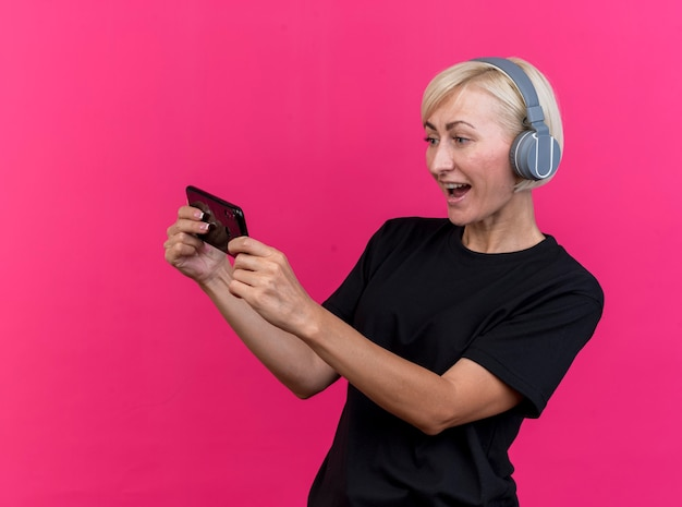 コピースペースで深紅色の背景に分離された携帯電話を保持し、見ているヘッドフォンを身に着けている縦断ビューに立っているうれしそうな中年金髪スラブ女性