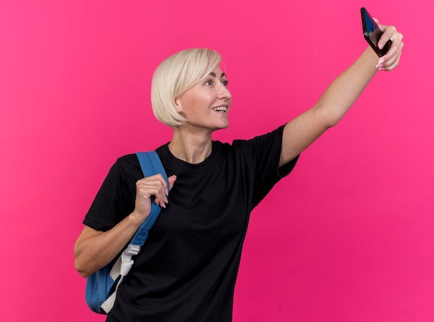 Joyful middle-aged blonde slavic woman wearing back pack holding strap of back pack taking selfie isolated on pink wall