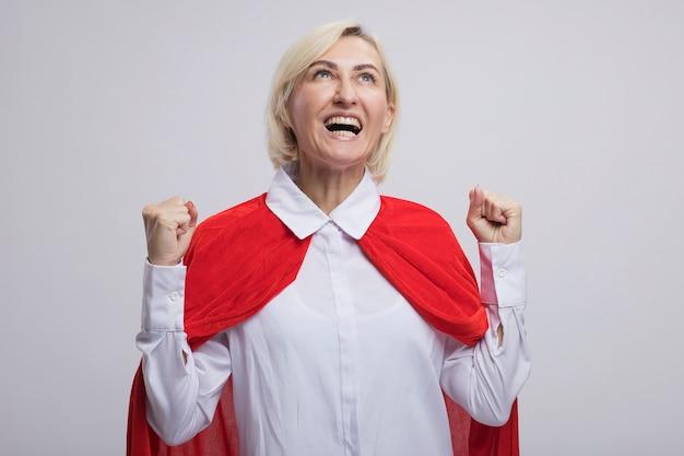 Donna bionda di mezza età allegra del supereroe in mantello rosso che fa sì il gesto che guarda in su