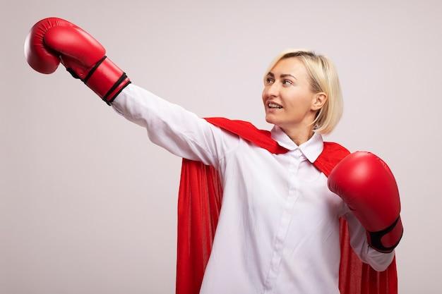 Donna bionda di mezza età allegra del supereroe in mantello rosso che indossa i guanti della scatola che allungano il pugno che esamina lato isolato sulla parete bianca