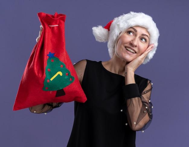 Gioiosa donna bionda di mezza età che indossa il cappello di natale che tiene il sacco di natale tenendo la mano sul viso guardando in alto isolato su sfondo viola