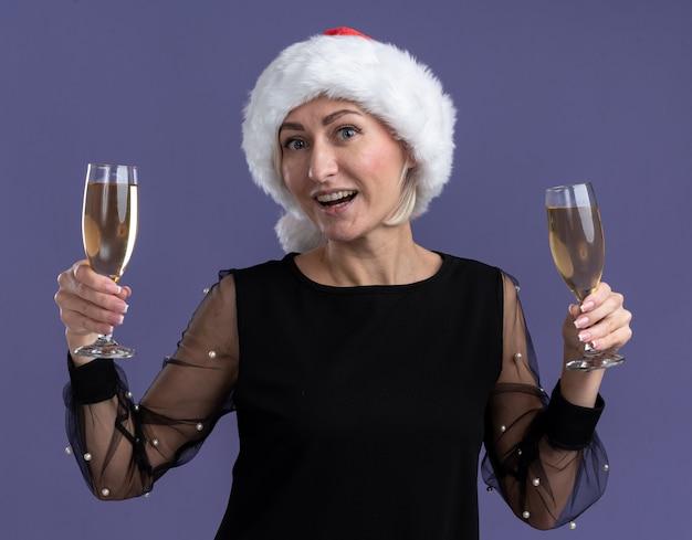 Радостная блондинка средних лет в новогодней шапке смотрит в камеру с двумя бокалами шампанского, изолированными на фиолетовом фоне