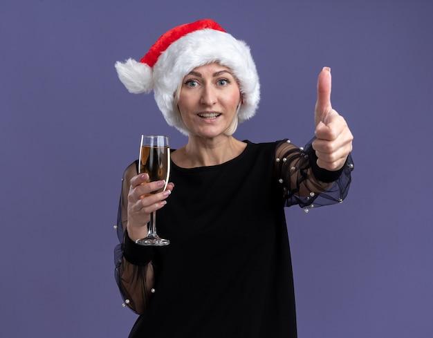 Gioiosa donna bionda di mezza età che indossa il cappello di natale guardando la telecamera tenendo un bicchiere di champagne che mostra il pollice in alto isolato su sfondo viola