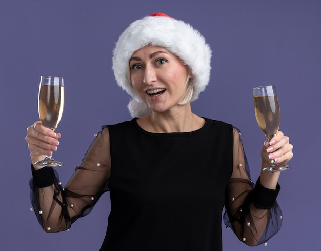Joyful middle-aged blonde woman wearing christmas hat looking at camera holding two glasses of champagne isolated on purple background