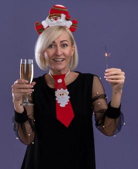 Радостная блондинка средних лет в головной повязке санта-клауса и галстуке держит праздничный бенгальский огонь и бокал шампанского, глядя в камеру, изолированную на фиолетовом фоне