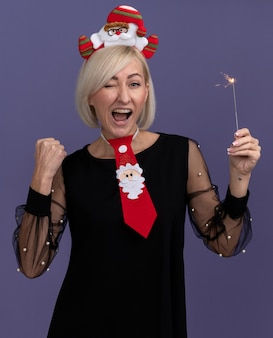 サンタクロースのヘッドバンドとネクタイを身に着けているうれしそうな中年のブロンドの女性は、紫色の背景に分離されたはいジェスチャーをしているカメラウィンクを見て休日の線香花火を保持しています