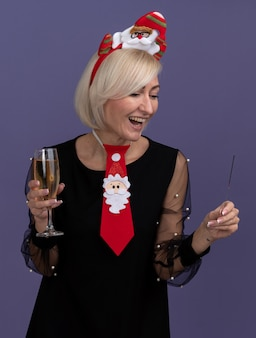 Joyful middle-aged blonde woman wearing santa claus headband and tie holding holiday sparkler and glass of champagne looking at sparkler isolated on purple background