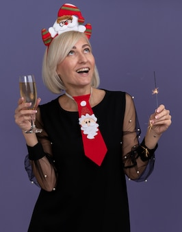 Joyful middle-aged blonde woman wearing santa claus headband and tie holding holiday sparkler and glass of champagne looking up isolated on purple background