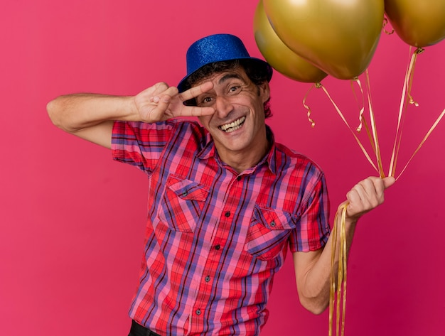 Joyful middle-aged caucasian party man wearing party hat holding balloons looking at camera doing peace sign isolated on crimson background
