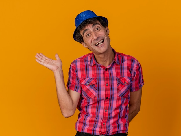 Joyful middle-aged caucasian party man wearing party hat looking at camera showing empty hand keeping another one behind back isolated on orange background with copy space