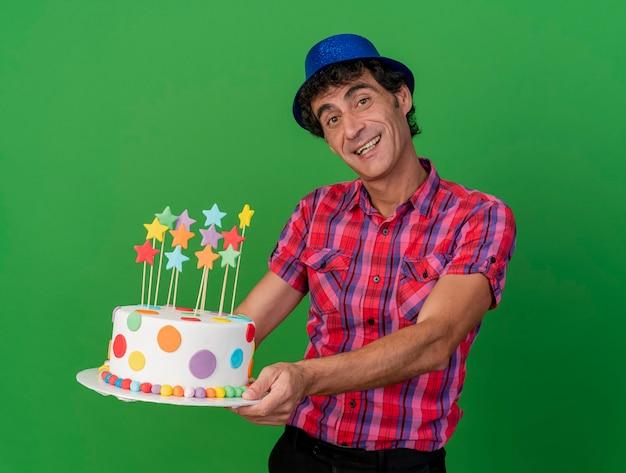 緑の背景に分離されたカメラを見てバースデーケーキを伸ばしてパーティーハットを身に着けているうれしそうな中年白人パーティー男