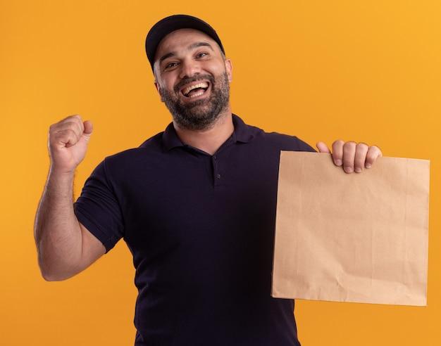Радостный курьер среднего возраста в униформе и кепке держит бумажный пакет с едой, показывая жест да, изолированный на желтой стене