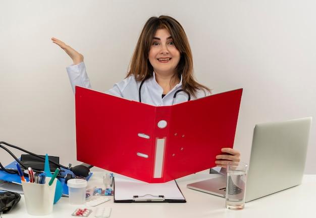 医療用ローブと聴診器を身に着けているうれしそうな中年の女性医師は、医療ツールクリップボードとラップトップ保持フォルダーと空の手を分離して机に座っています