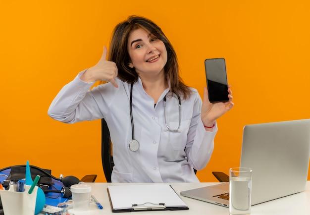Medico femminile di mezza età gioioso che indossa veste medica e stetoscopio seduto alla scrivania con appunti di strumenti medici e laptop facendo gesto di chiamata che mostra il telefono cellulare isolato