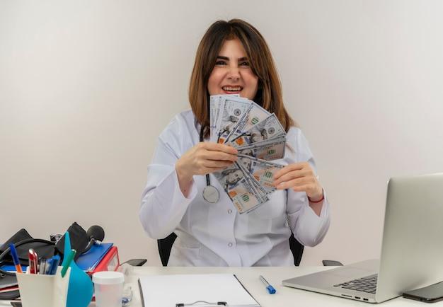 Medico femminile di mezza età gioioso che indossa veste medica e stetoscopio seduto alla scrivania con appunti di strumenti medici e laptop con denaro isolato