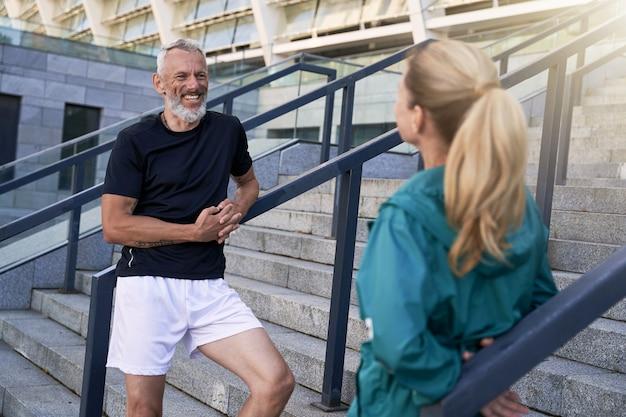 朝のトレーニングの後に屋外に立っている間、スポーティーな女性とおしゃべりするうれしそうな中年の男