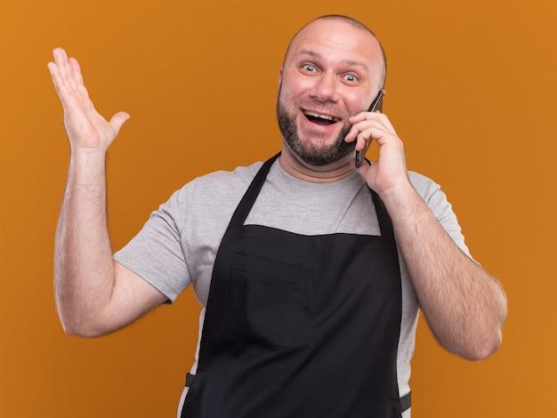 Il gioioso barbiere maschio di mezza età in uniforme parla al telefono alzando la mano isolata sul muro arancione