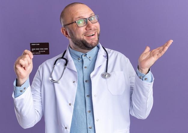 紫色の壁に隔離された空の手を示すクレジットカードを保持している眼鏡と医療ローブと聴診器を身に着けているうれしそうな中年男性医師