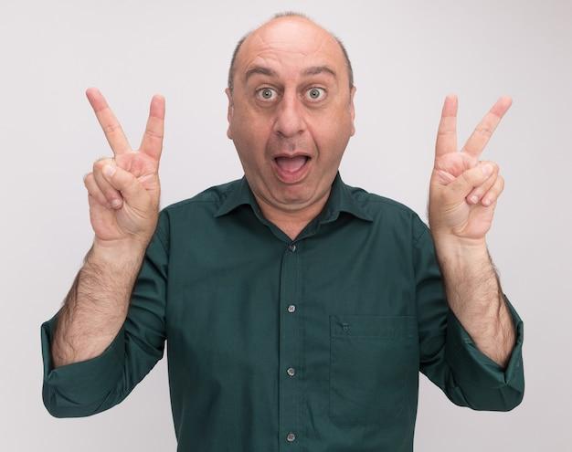 Gioioso uomo di mezza età che indossa la maglietta verde che mostra il gesto di pace isolato sul muro bianco