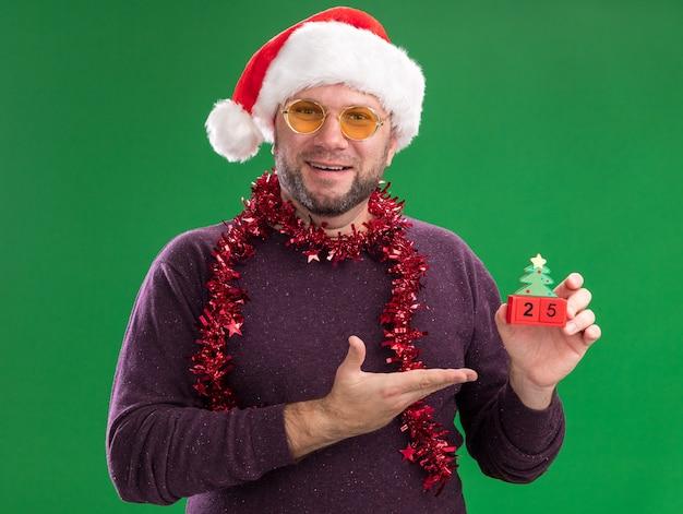 Радостный мужчина средних лет в новогодней шапке и мишурной гирлянде на шее в очках, держащий и указывающий рукой на елочную игрушку с датой, смотрящий в камеру, изолированную на зеленом фоне
