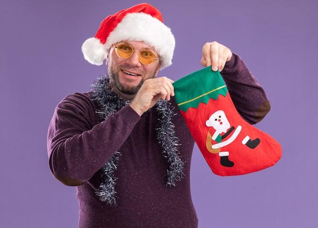 Радостный мужчина средних лет в шляпе санта-клауса и гирлянде из мишуры на шее в очках держит рождественский чулок, изолированный на фиолетовой стене