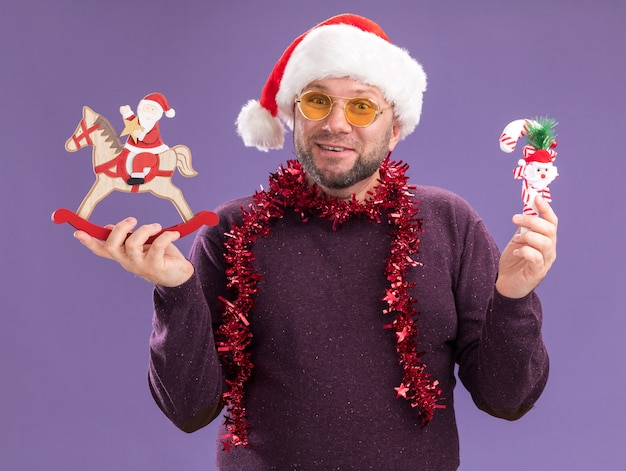 Joyful middle-aged man wearing santa hat and tinsel garland around neck with glasses holding candy cane ornament and santa on rocking horse figurine  isolated on purple wall