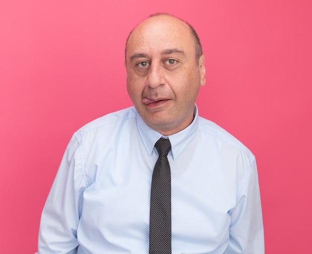 Радостный мужчина средних лет в белой футболке с галстуком показывает язык на розовой стене
