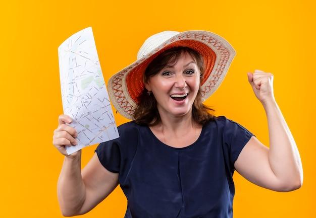 지도를 들고 격리 된 노란색 벽에 예 제스처를 보여주는 모자에 즐거운 중년 여행자 여자