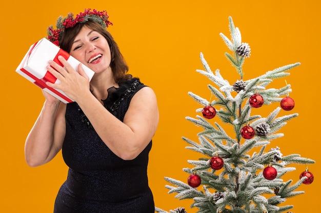 크리스마스 머리 화환과 장식 된 크리스마스 트리 근처에 서있는 목 주위에 반짝이 화환을 입고 즐거운 중년 여성