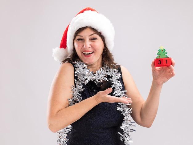 サンタの帽子と見掛け倒しの花輪を首に抱いて、白い背景で隔離のカメラを見て日付とクリスマスツリーのおもちゃを指してうれしそうな中年女性