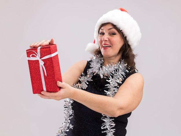 白い背景で隔離のカメラを見てクリスマスプレゼントパッケージを保持している首にサンタの帽子と見掛け倒しの花輪を身に着けているうれしそうな中年女性