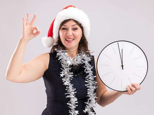 サンタの帽子と見掛け倒しのガーランドを首に身に着けているうれしそうな中年の女性は、白い背景で隔離のokサインをしているカメラを見て時計を保持しています
