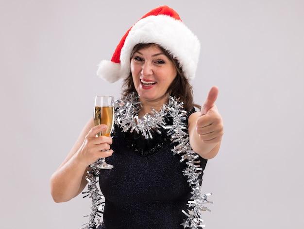サンタの帽子と見掛け倒しのガーランドを首に身に着けているうれしそうな中年の女性は、コピースペースで白い背景に分離された親指を示すカメラを見てシャンパンのガラスを保持しています