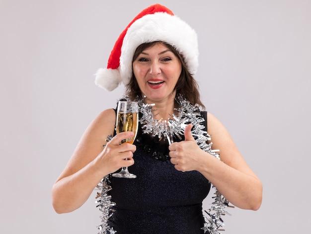 サンタの帽子と見掛け倒しの花輪を首に身に着けているうれしそうな中年の女性は、白い背景で隔離の親指を示すカメラを見てシャンパンのガラスを保持しています