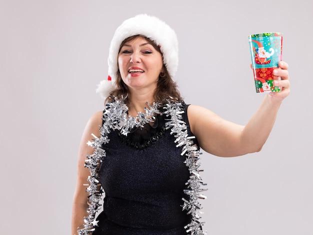 흰색 배경에 고립 된 카메라를보고 카메라를 향해 플라스틱 크리스마스 컵을 뻗어 목 주위에 산타 모자와 반짝이 갈 랜드를 입고 즐거운 중년 여성