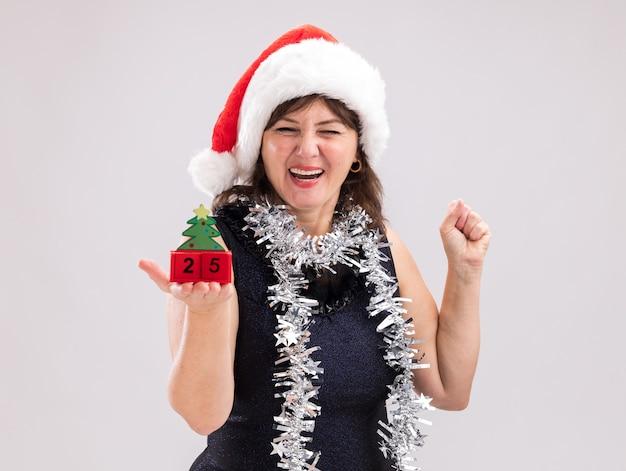 Gioiosa donna di mezza età che indossa un cappello da babbo natale e una ghirlanda di orpelli intorno al collo che tiene il giocattolo dell'albero di natale con la data che guarda l'obbiettivo facendo sì gesto isolato su sfondo bianco