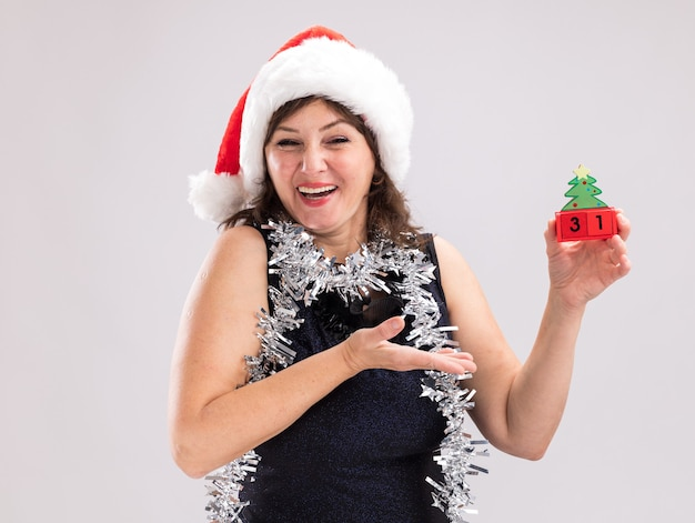 Gioiosa donna di mezza età che indossa cappello da babbo natale e ghirlanda di orpelli intorno al collo tenendo e puntando al giocattolo dell'albero di natale con data guardando la fotocamera isolata su sfondo bianco