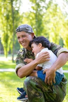 ミッション旅行から戻った後、屋外で男の子を抱き締めて、幼い息子を腕に抱いてうれしそうな軍のお父さん。垂直ショット。家族の再会または帰国の概念