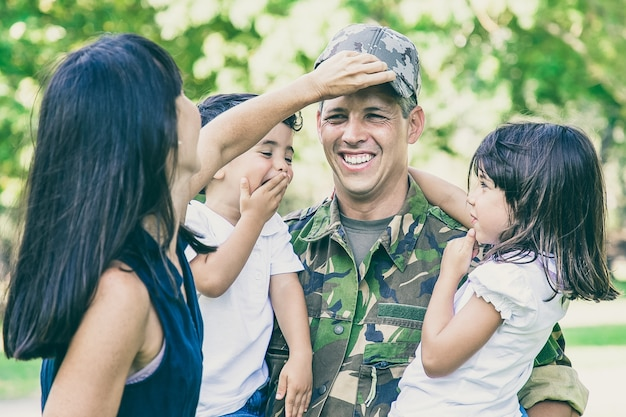 Joyful military father in uniform returning to family, holding two kids in arms
