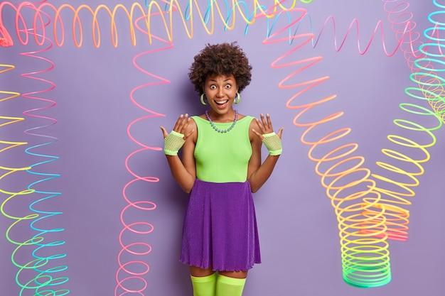 Радостная миллениальная девушка поднимает руки, носит спортивные перчатки, модную красочную одежду, дурачится, веселится на вечеринке, позирует в помещении с разноцветными обтягивающими игрушками. молодость