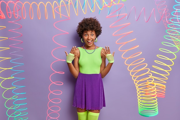 Joyful millennial girl raises hands, wears sport gloves, fashionable colorful outfit, fools around, has fun on party, poses indoor with colorful slinky toys around. youth