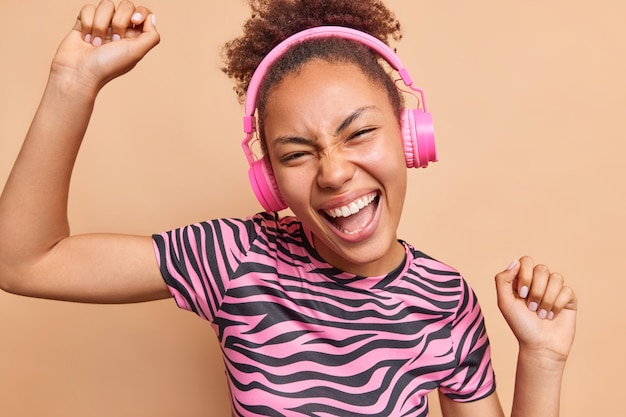 Joyful millennial woman dances with arms raised up smiles broadly enjoys favorite music from playlist wears wireless headphones dressed in casual clothes isolated over beige wall